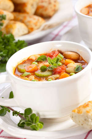 Closeup of bowl of hot fresh Minestrone soup and cheese garlic breadsticks