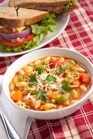 minestrone: Closeup of bowl of hot fresh Minestrone soup and whole wheat bread turkey sandwich