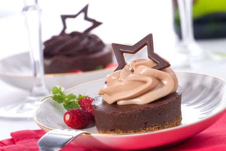 Coppia di cheesecake delizioso cioccolato servita con fragole e menta fresca. Flute di champagne. Ornamenti di Natale fuori fuoco in background