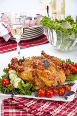 Whole roasted chicken garnished with fresh cucumbers, wine tomatoes, green salad and sage on dinner table Banque d'images