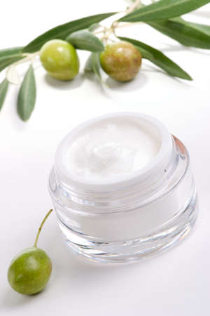 moisturizing: Closeup of jar of moisturizing face cream and twig with green olives.