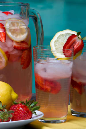 Two glasses of home made iced cold pink strawberry lemonade and pitcher on hot summer on edge of swimming pool.  photo