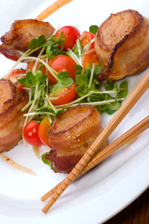 Close-up van Ginger Soy Sint-Jakobsschelpen omwikkeld met bacon gegarneerd met verse kerstomaten en Daikon kiemen.