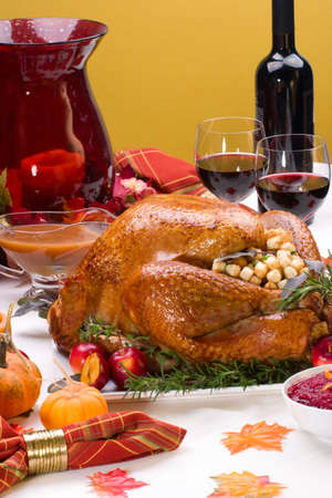 Garnished roasted turkey on holiday decorated table with pumpkins and glasses of red wine photo