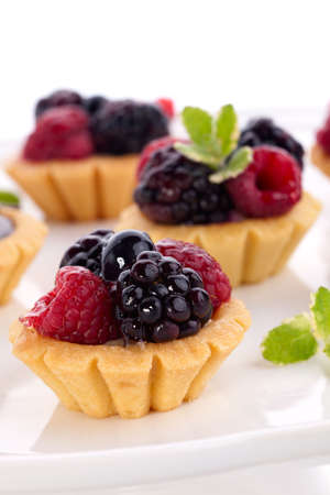 Full tray of delicious fresh berry cakes garnished with pineapple mint photo