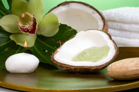 Avocado coconut scrub in coconut shell, orchid flower (Cymbidium sp.), tropical plant, soap and aroma candle. Suited for relaxing and health commercials photo