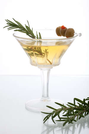 olive green: Glass of Rosemary Martini - gin, vodka, garnished with fresh rosemary sprig and olives Stock Photo