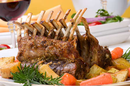 lamb chop: Rack of Lamb (ribs) with Rosemary garlic dressing, garnished with baby carrots, potatoes and rosemary sprigs. Dinner settings.
