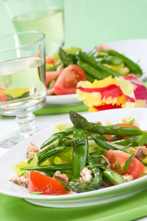 green salad: Two plates of asparagus, snow pea and tomato salad with ginger dressing