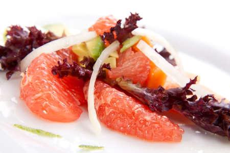 Closeup of papaya, avocado and grapefruit salad with sweet onion and lime wedges Stock Photo