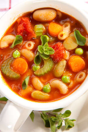 minestrone: Closeup of bowl of hot fresh Minestrone soup and cheese garlic breadsticks