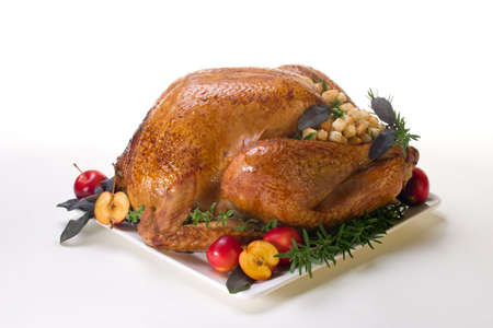 Garnished roasted turkey on platter over white background Stock Photo