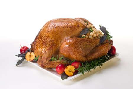 stuffing: Garnished roasted turkey on platter over white background Stock Photo