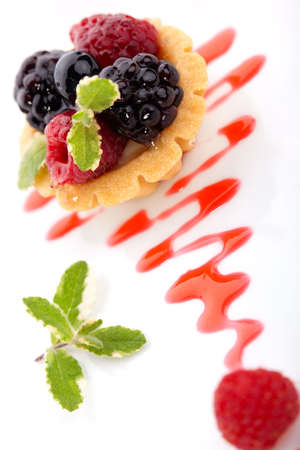 Closeup of delicious fresh berry cake garnished with pineapple mint photo