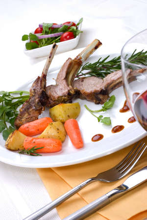 Lamb chops (ribs) with Rosemary garlic dressing, garnished with carrots, potatoes and rosemary sprigs. Dinner settings. Stok Fotoğraf