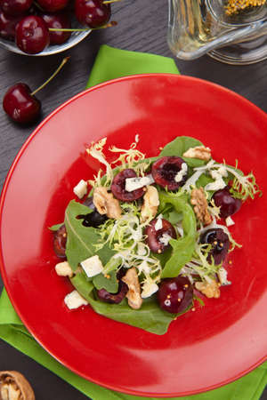 Green salad with cherries, walnuts and blue cheese. Fresh cheries around. Saucer with vinaigrette.