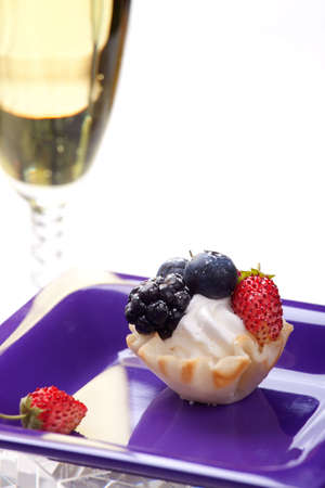Closeup of delicious fresh berry cake and glass of champagne photo