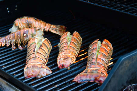 Closeup of delicious juicy lobster tails is grilling on open fire photo