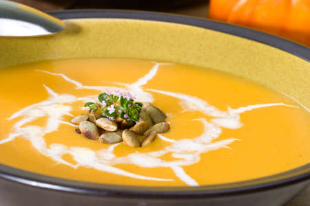 Closeup of bowl of hot delicious pumpkin soup garnished with cream, roasted pumpkin seeds and fresh thyme photo