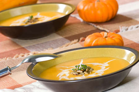 Two bowls of hot delicious pumpkin soup garnished with cream, roasted pumpkin seeds and fresh thyme photo