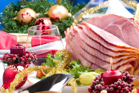 Holiday table setting with delicious whole baked sliced ham, marinated peppers, cherry tomatoes, vegetable salad and glasses of red wine.