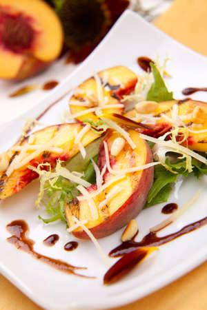pignons de pin: Gros plan de la salade de p�ches grill�es avec du fromage parmesan et pignons grill�s. Sauce au vinaigre balsamique.