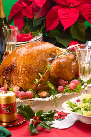 garnished: Garnished roasted turkey on Christmas decorated table with candles and flutes of champagne