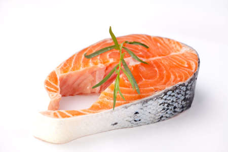 Closeup of raw uncooked fresh salmon steak on white plate garnished with tarragon ready to grill