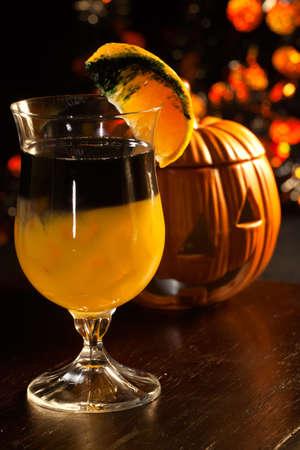 Closeup of Rotten Pumpkin Cocktail, black vodka, orange juice - Halloween drinks series