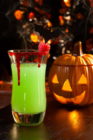 Closeup of Vampires Kiss Cocktail, rum, melon liqueur, soda and touch of tabasco, garnished with fresh raspberry - Halloween drinks series Stok Fotoğraf