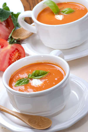 Two bowls of delicious tomato soup garnished with cream and basil leaves