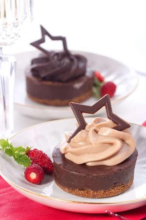 Coppia di torta al cioccolato servita con fragole fresche e menta. Flute di champagne. Ornamento di Natale fuori fuoco in background