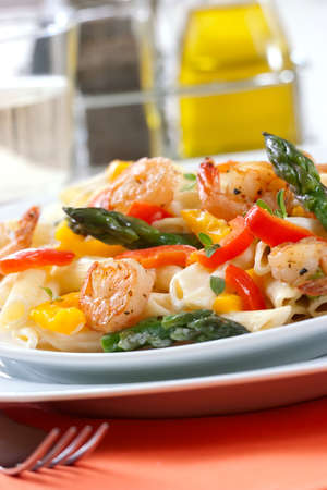 shallow dof: Shrimp Penne (tube-shaped pasta) with asparagus, bell pepper, origan and creamy Alfredo sauce . Green salad. Shallow DOF