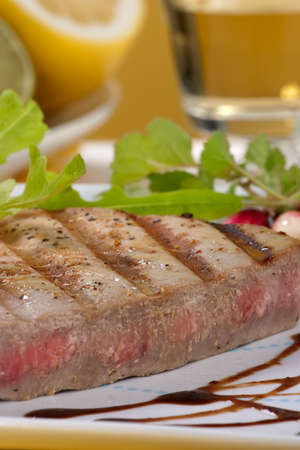Juicy delicious Citrus-peppercorn-spiked grilled tuna steak with grilled vegetables photo