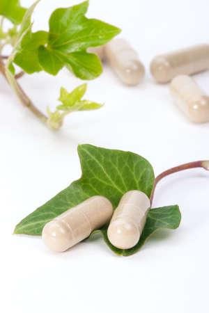 medicamentos: Primer plano de p�ldoras de suplementos de hierbas y hojas frescas de hiedra m�s adecuado para los anuncios de la medicina alternativa. Shallow DOF.