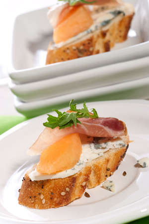 Closeup of two delicious Prosciutto canapes-sandwiches made from cantaloup melon, blue cheese, Prosciutto ham and salad.  photo