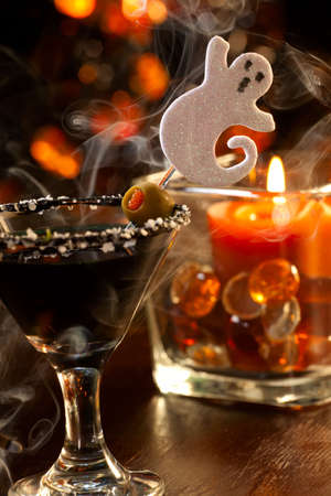 Closeup of Scary Martini, black vodka, vermouth, garnished with olive - Halloween drinks series photo