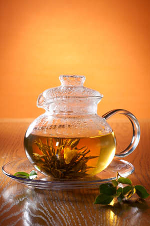 Transparent glass teapot with Chinese green tea. Jasmine flower inside. Stock Photo