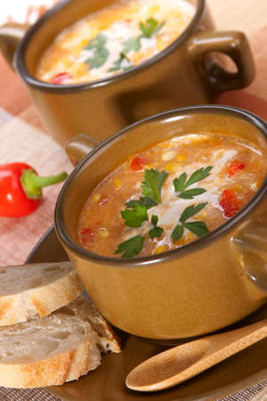 chowder: Bowls of hot delicious corn and red chilli chowder garnished with cream and fresh parsley Stock Photo