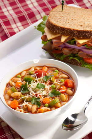 Closeup of bowl of hot fresh Minestrone soup and whole wheat bread turkey breast sandwich photo