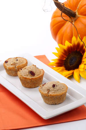 Full plate of just baked whole grain home made Cranberry-walnut muffins in fall environment. Copyspace. photo