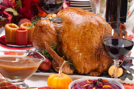 gravy: Garnished roasted turkey on holiday decorated table with pumpkins and glasses of red wine