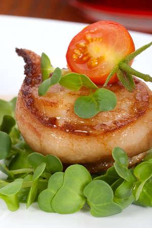 Close-up van Ginger soja coquilles verpakt door bacon gegarneerd met verse cherry tomaten en daikon spruiten. Stockfoto