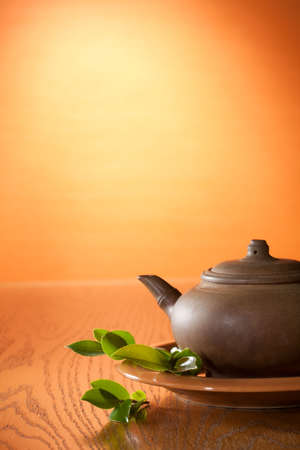 chinese teapot: Clay teapot with Chinese green tea. Tea leaves. Stock Photo