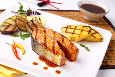 Delicious grilled Teriyaki salmon steak  garnished with grilled pineapple, baby eggplants, zucchini and chilli pepper for healthy style dinner. photo