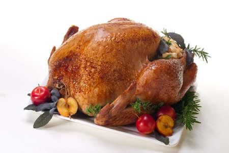 Garnished roasted turkey on platter over white background