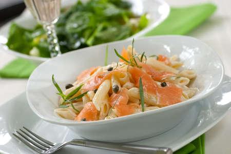 Gerookte zalm penne (pasta buis-vormige) met cappers, Dragon en kaas romige saus. Caesar salade en een glas witte wijn onscherp. Ondiep DOF