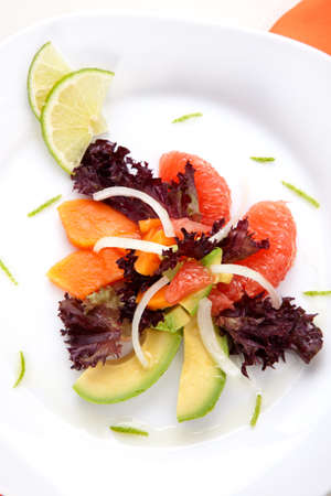 Closeup of papaya, avocado and grapefruit salad with sweet onion and lime wedges photo