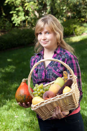 Teenage girl holding a basket of fruits and vegetables. photo