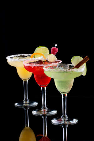cocktails: Three Margaritas - apple, orange and raspberry - in chilled glasses over black background, garnished with slice of green apple, limes, orange twist, raspberry and cinnamon stick. Most popular cocktails series. Stock Photo